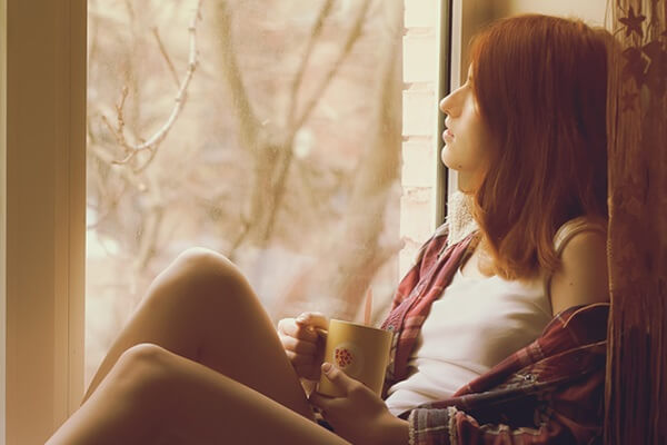 Teen gazing out window, worried about her parent's divorce