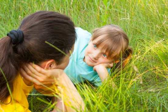 Mom and daughter having a discussion about divorce while laying in the grass.