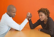 Image of a man and woman arm wrestling