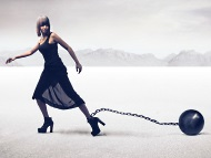 Woman dragging around a ball and chain