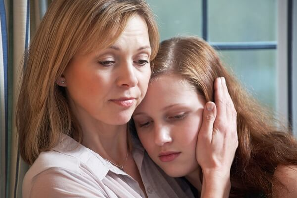 Mother being strong and comforting daughter after divorce