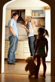 Child in doorway watching parents fight