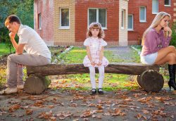 Parents divided with child sitting on a bench in the middle