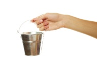 Woman's hand holding a small metal pail