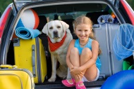 Girl and dog in car packed for summer vacation