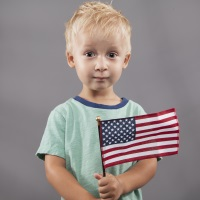 partriotic little boy holding United States flag