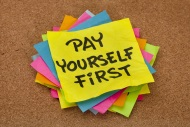 Pay Yourself First sticky note on cork-board