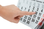 Woman's hand pointing to date on calendar