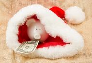 Cute piggy bank hiding in Santa's cap to save money for Christmas