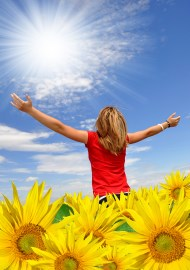 Woman in sunflower field facing the sun and embracing life