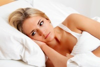 Troubled woman lying awake in bed wondering what she should do