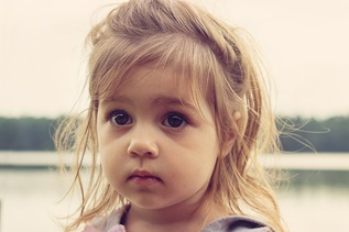 Wide-eyed little girl unaware of custody struggles