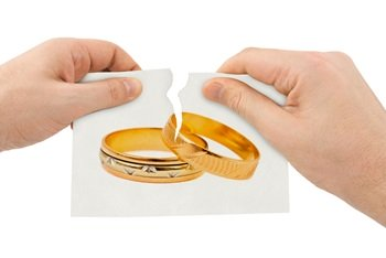 Hands tearing up picture of wedding rings