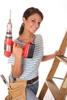 handy woman with drill doing home repairs
