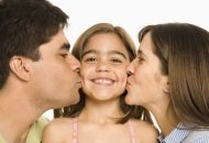 Young girl being kissed by both mom and dad