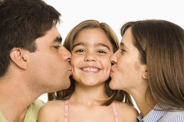 Young girl being kissed by both mom and dad.