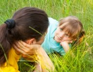 Mom and daughter having discussion while laying in the grass