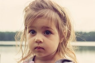 Wide-eyed little girl unaware of custody struggles